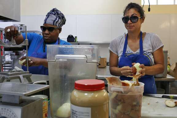 Reem Assil, right, grimaces as she and Wanda Kruda prepare 50 lbs of onions  with sunglasses on to protect their eyes from the fumes during production day at La Cocina Community Kitchen Oct. 11, 2016 in San Francisco, Calif.
