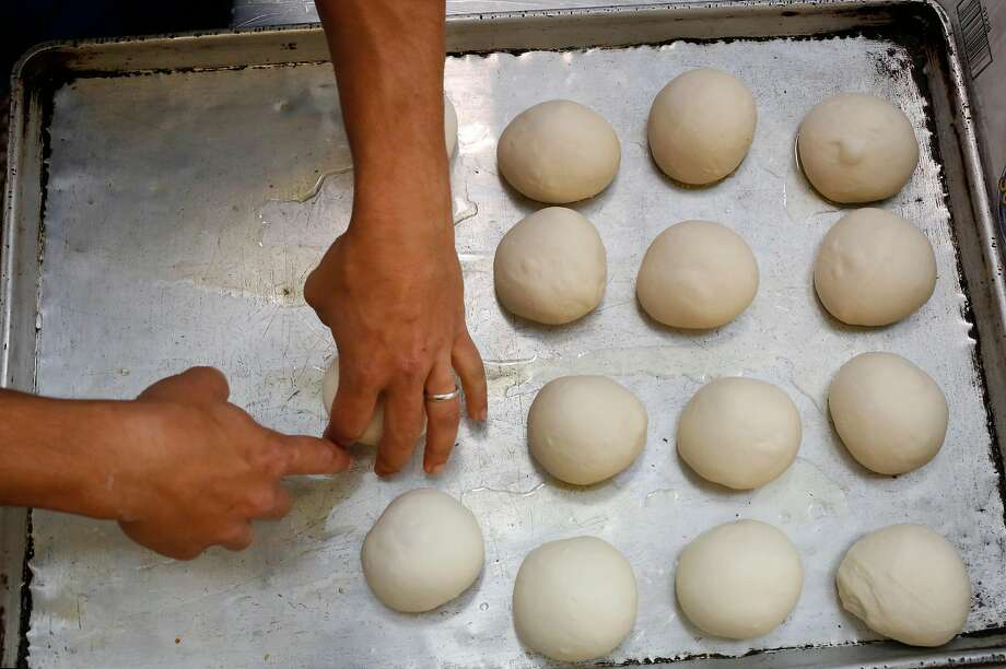 Reem Assil places carefully shaped boules on a baking pan during production day for Reem's at La Cocina incubator kitchen in San Francisco. Photo: Leah Millis, The Chronicle