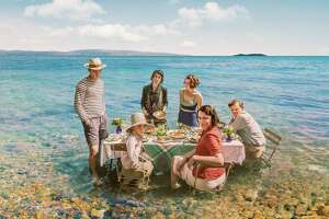 The British Durrell family, led by mom Louisa (Keeley Hawes, front row right), keeps cool by dining in the calm Greek sea in the six-part PBS series, 'The Durrells in Corfu.'