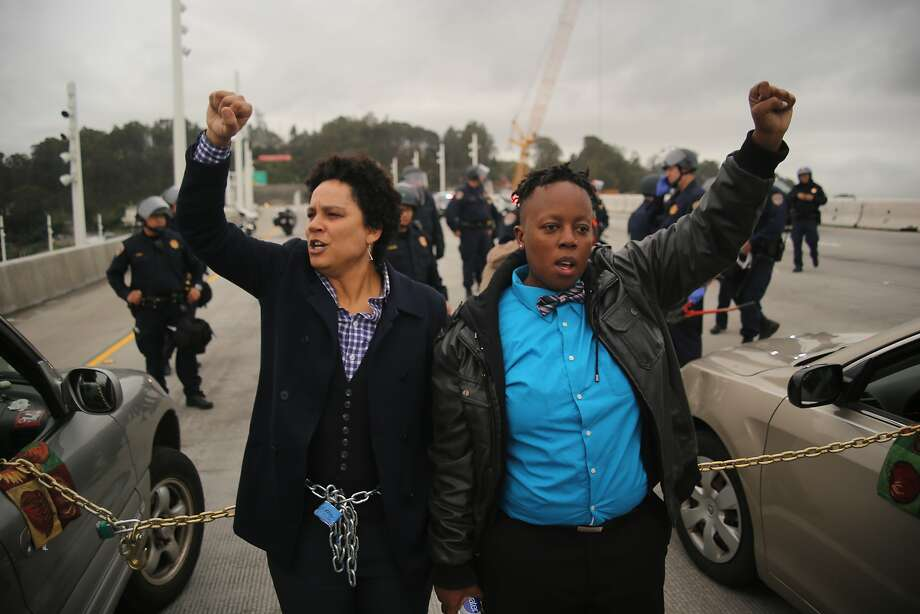 Kathryn Snyder (left) and Nolizwe Nondabula (right) raise their fists as they block traffic during a demonstration against police brutality on the eastern span of the San Francisco-Oakland Bay Bridge in January. Photo: Joel Angel Ju�rez