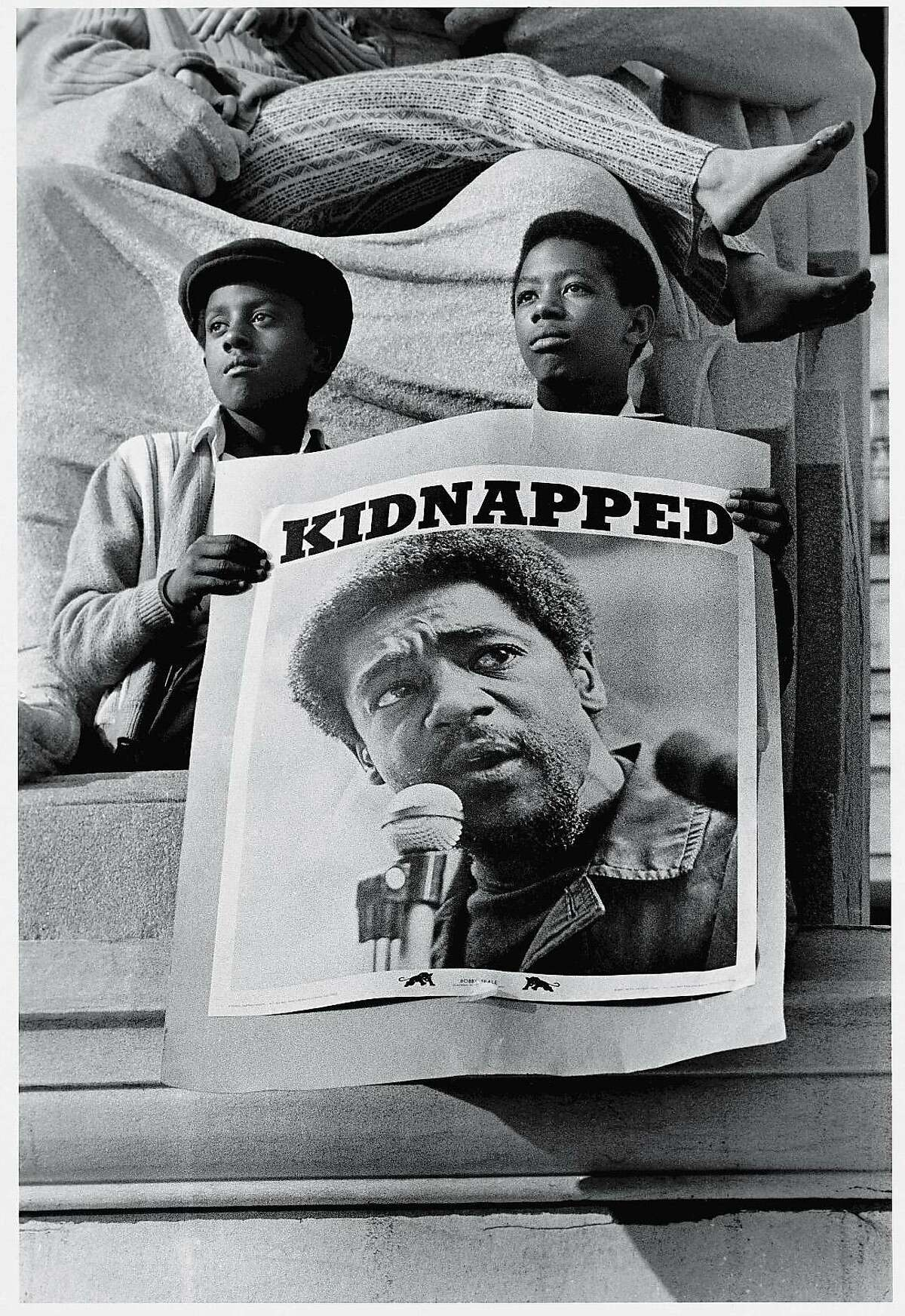 At a rally in support of the Black Panther Party, two young men hold poster of Panther leader Bobby Seale under the heading 'Kidnapped,' New Haven, Connecticut, May 1, 1970. The poster refers to the trial of the New Haven Nine, of which Seale was one, which had just begun.