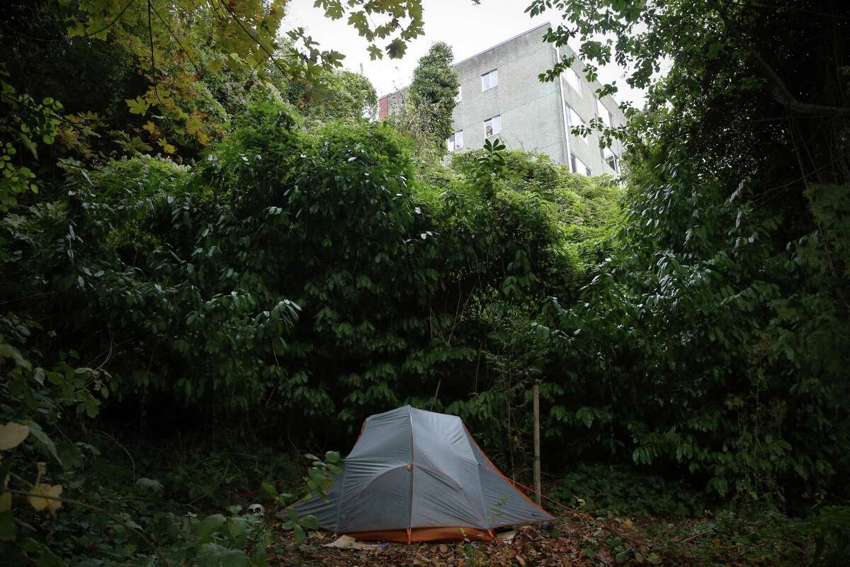 A solitary tent is set up in a wooded area a few feet from the tennis courts at Kinnear Park in Queen Anne.