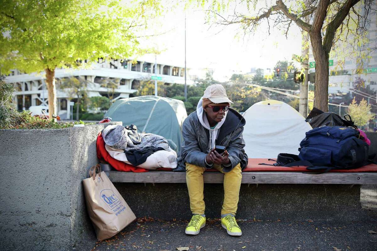 Joyce Gunn listens to her radio outside her tent at the corner of Denny Way and Broad Street where a small encampment has sprung up in recent weeks. Gunn has been homeless since 2011 and moves around the city to different spots.