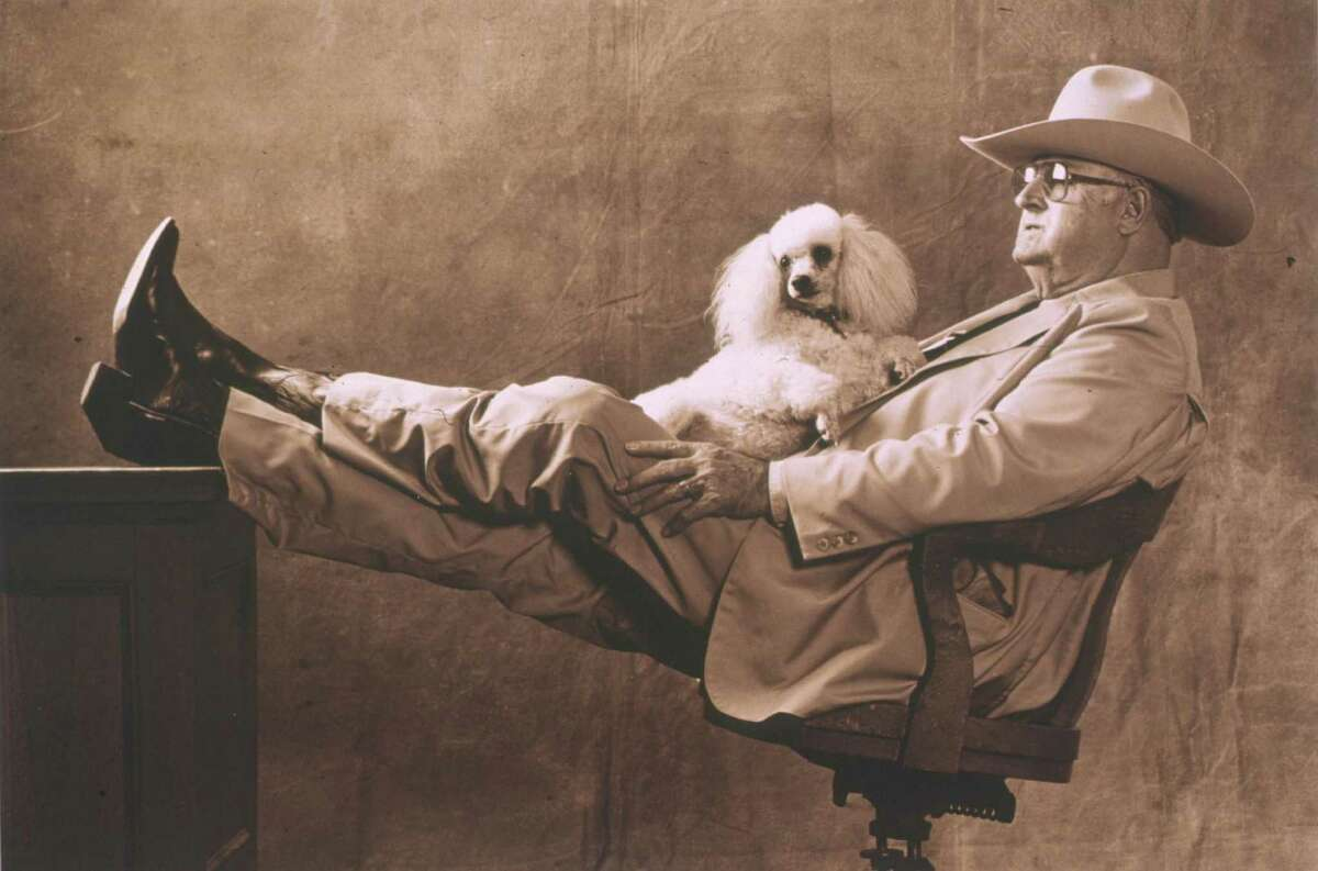 """Sheriff Rufe Jordan. HOUCHRON CAPTION (04/16/1998): Sheriff Rufe Jordan with poodle, Honey, was taken by photographer Kent Barker for a feature story published in 1984. This photo of the Gray County sheriff is part of an exhibit titled """"The Pictures of Texas Monthly: Twenty-Five Years"""" at the Houston Center for Photography:"""
