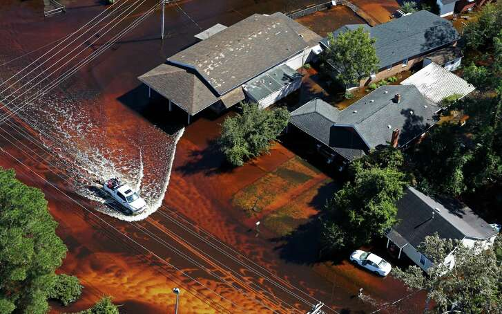 A truck drives through floodwaters from Hurricane Matthew in Lumberton, N.C., Wednesday, Oct. 12, 2016. People were ordered to evacuate, and officials warned that some communities could be cut off by washed out roads or bridge closures. (AP Photo/Chuck Burton)