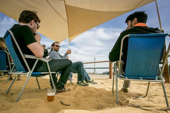 People have beers on the beach at the Woods Island Club in San Francisco, Calif. on October 13th, 2016.