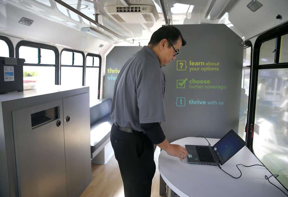 Rich Manuzon sets up a Covered California health care coverage enrollment van operated by Kaiser Permanente in Oakland in 2015. For 2017, many Covered California customers are facing larger premium increases. Photo: Paul Chinn, The Chronicle