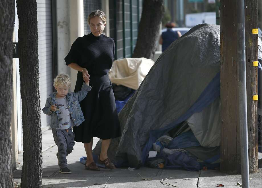 Jennine Jacob walks with 3-year-old son Jasper past homeless encampments after playing at Potrero del Sol Park in San Francisco. Photo: Paul Chinn, The Chronicle