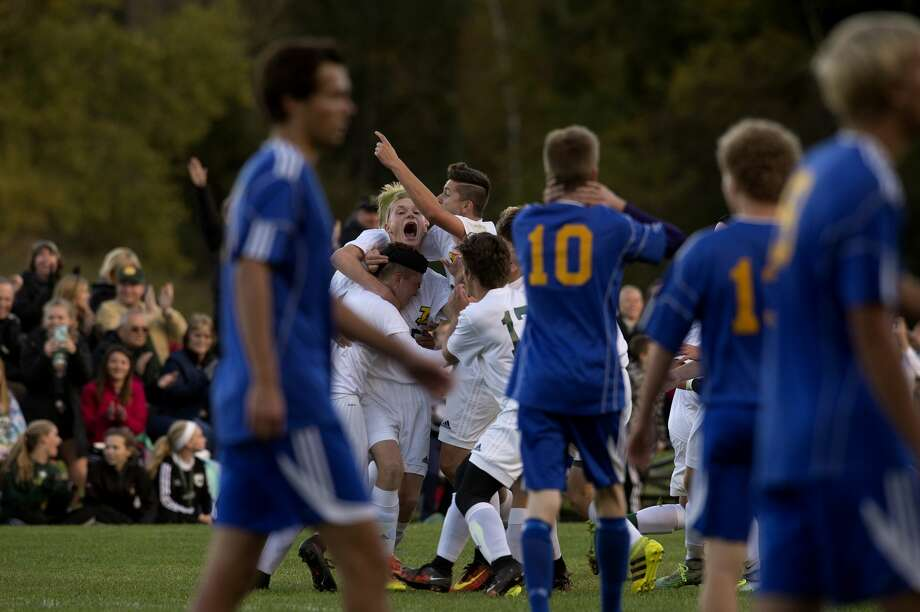 Dow High soccer team celebrate NAME's goal in the second half of the Thursday evening game against Midland High. Dow defeated Midland 3-0. Photo: Brittney Lohmiller/Midland Daily News/Brittney Lohmiller