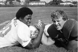 Earl Campbell, left, and Steve Freydenfeldt engage in some friendly arm wrestling before the 40th All-Star High School football game in 1974.