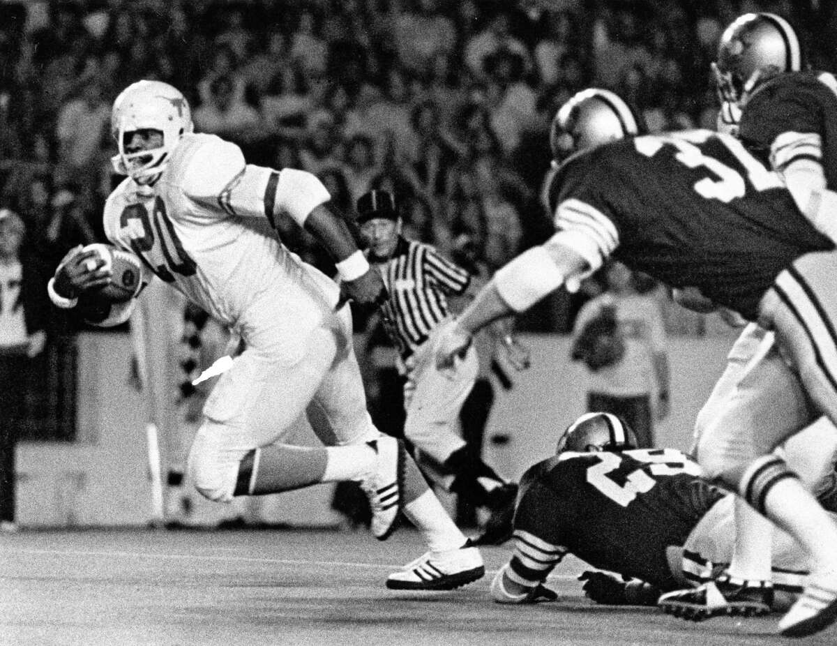 10/26/1974 - Texas Longhorns v Rice Owls. Longhorns running back Earl Campbell (20) pulls away from Owls defense at Rice Stadium.