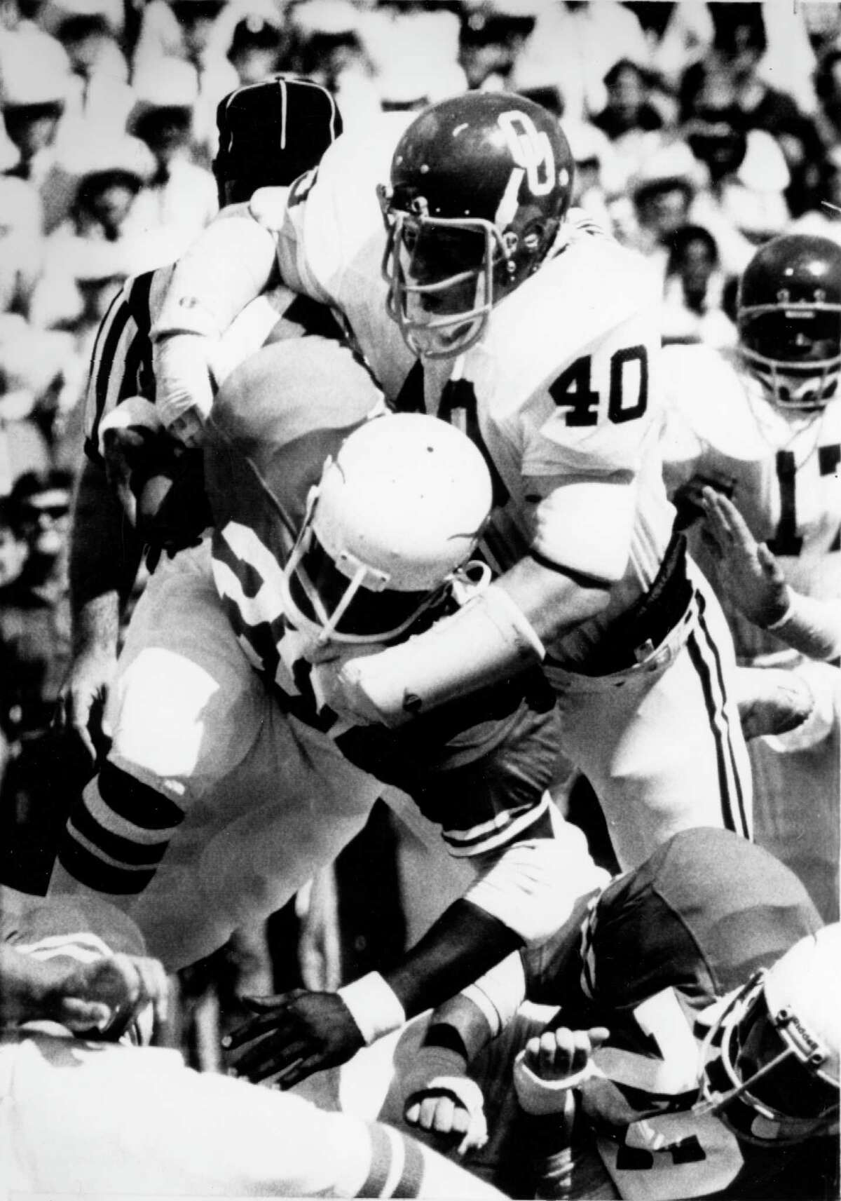 10/11/1975 - Texas Longhorns v Oklahoma Sooners. Longhorns running back Earl Campbell (20) is stopped by Sooners Bill Dalke (40) for a 3-yard gain up the middle in the first quarter in Cotton Bowl stadium in Dallas.