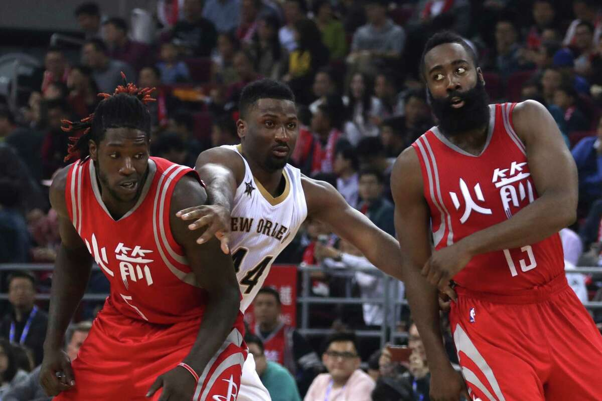 Solomon Hill of the New Orleans Pelicans pushes apart Montrezl Harrell of the Houston Rockets, left and James Harden of the Houston Rockets during a preseasons NBA game in Beijing, China, Wednesday, Oct. 12, 2016. (AP Photo/Ng Han Guan)