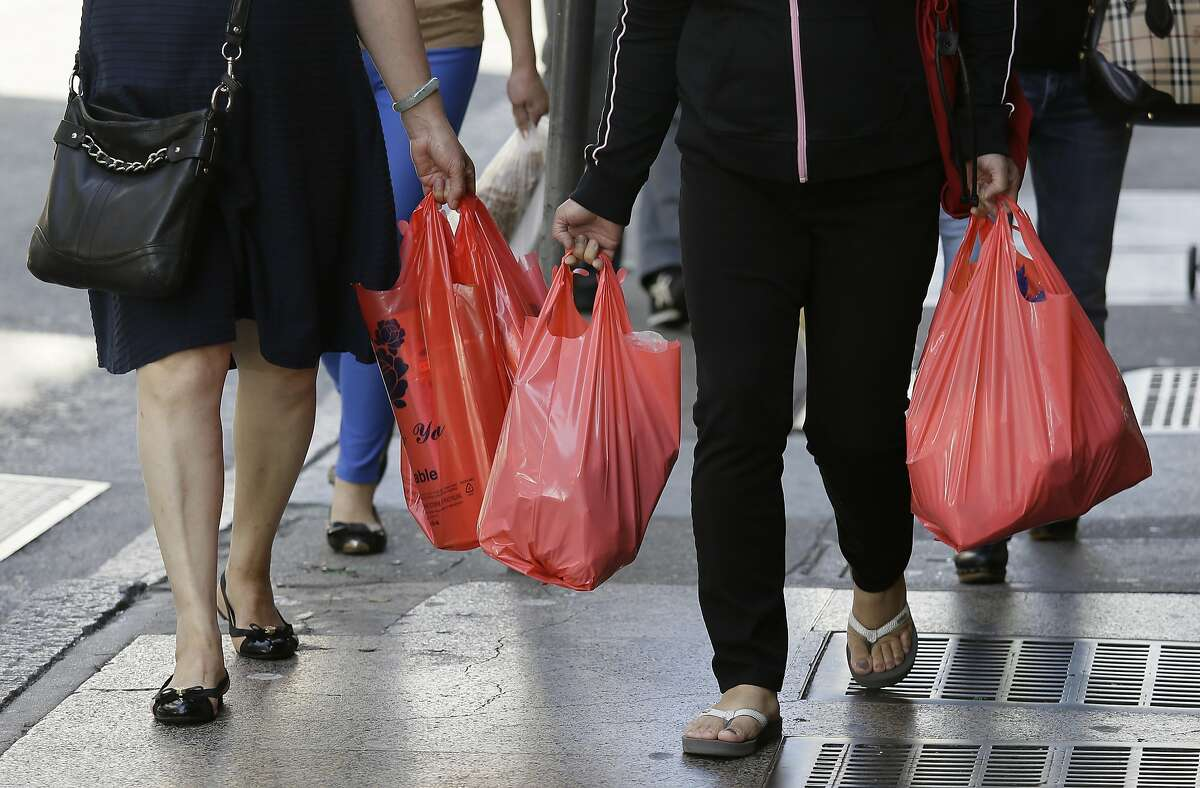 In this photo taken Tuesday, Sept. 20, 2016, women walk with plastic bags through Chinatown in San Francisco. California voters are considering a November referendum that would uphold or overturn a statewide ban on single-use plastic carryout bags.
