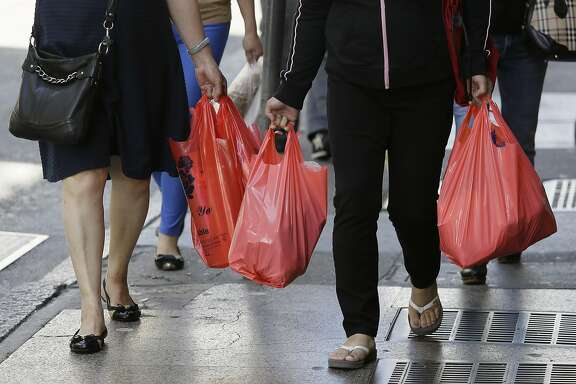 In this photo taken Tuesday, Sept. 20, 2016, women walk with plastic bags through Chinatown in San Francisco. California voters are considering a November referendum that would uphold or overturn a statewide ban on single-use plastic carryout bags. (AP Photo/Eric Risberg)