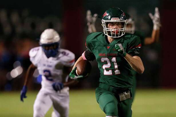 The Woodlands' linebacker Grant Milton (21) returns an interception 50 yards for a touchdown in the second quarter of Thursday night's game against Oak Ridge.