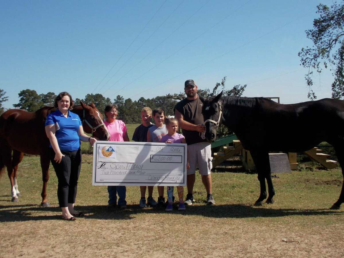 Sam Houston Electrical Cooperation Charitable Foundation representatives present a check to Donna Wiebelhaus, SpiritHorse executive director; riders Jaxon, Colton, and Colbie Lynn; and volunteer Colby Thompson.