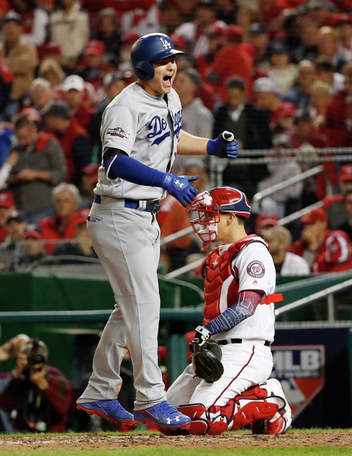 Los Angeles Dodgers' Joc Pederson celebrate as he crosses the plate to score past Washington Nationals catcher Jose Lobaton (59) on a solo home run during the seventh inning of Game 5 of baseball's National League Division Series at Nationals Park, Thursday, Oct. 13, 2016, in Washington.