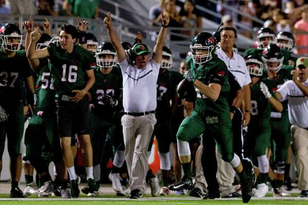 The Woodlands head coach Mark Schmid celebrates as linebacker Grant Milton (21) returns an interception for a 50-yard touchdown during the second quarter of a District 12-6A high school football game at Woodforest Bank Stadium Thursday, Oct. 13, 2016, in Shenandoah.