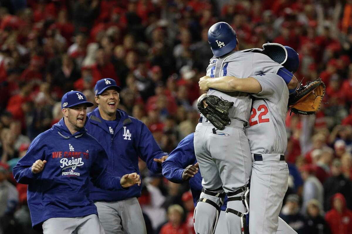 WASHINGTON, DC - OCTOBER 13: Clayton Kershaw #22 of the Los Angeles Dodgers celebrates with teammate Carlos Ruiz #51 after winning game five of the National League Division Series over the Washington Nationals 4-3 at Nationals Park on October 13, 2016 in Washington, DC.