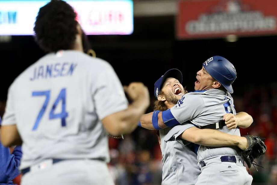 Catcher Carlos Ruiz hugs Clayton Kershaw as Kenley Jansen joins the Dodgers' celebration. Photo: Rob Carr, Getty Images
