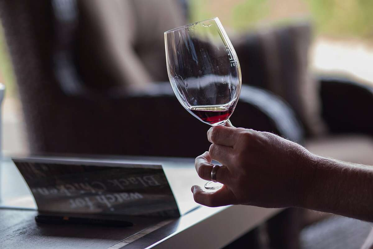 Ben Russet from Cincinnati Ohio look at his glass of Black Chicken Napa Valley Zinfandel during his appointment only tasting at Robert Biale Vineyards patio tasting room in Napa, California, USA 12 Oct 2016. (Peter DaSilva/Special to The Chronicle)
