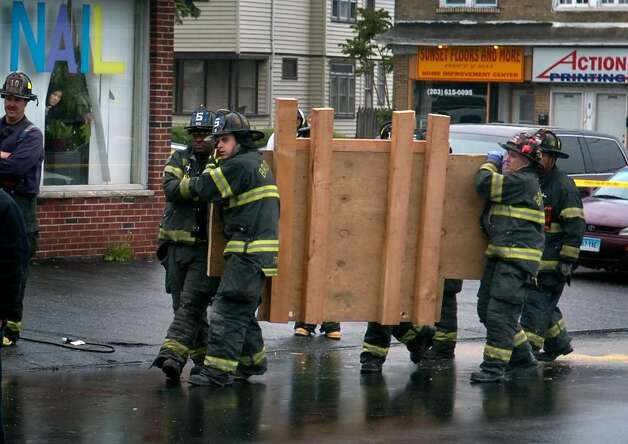 Firefighters carry a board to be used with a forklift to remove the body of an unidentified man, who officials said weighed nearly half a ton. The man died Tuesday night in his Boston Avenue home in Bridgeport, Conn. Part of the exterior of the building near a second floor window has been removed to make space to remove the man's body. Photo: Ned Gerard / Connecticut Post