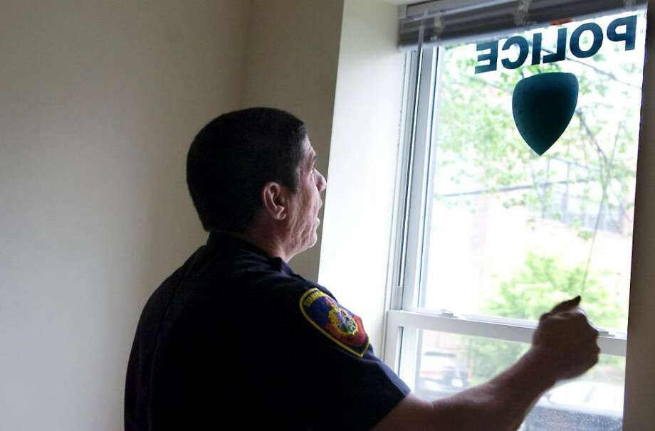 Lt. Nick Montagnese opens the blinds as Stamford police move into their new substation on Henry Street in Stamford, Conn. on Wednesday May 12, 2010. Photo: Kathleen O'Rourke / Stamford Advocate