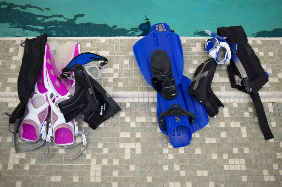 Shepherd residents Alexis McCaul and Kyle Sponseller's snorkeling gear is left on the side of the pool while they swim 250 yards at Northeast Middle School as part of their scuba rescue class Tuesday evening. The class is offered by Underwater Antics instructors Cheryl Roggenbuck and Tim Middleton. Photo: Brittney Lohmiller/Midland Daily News/Brittney Lohmiller