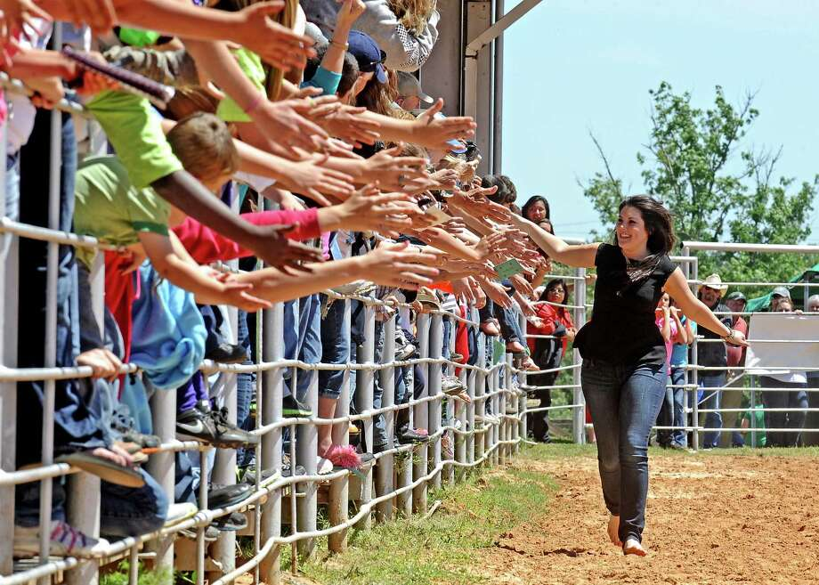 American Idol star Kree Harrison runs past fans during the taping of an episode at the Tyler County Rodeo Arena near her hometown of Woodville on Saturday, May 4, 2013.   Randy Edwards/The Enterprise
