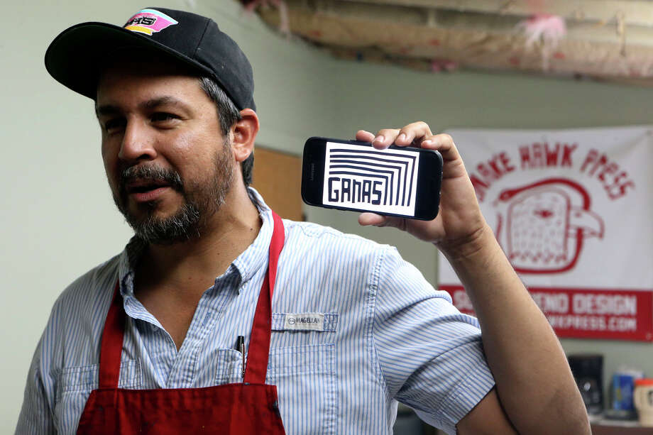 Artist Cruz Ortiz shows a rendering on his phone of the artwork he created that will be used for the Hillary Clinton campaign. Photo: John Davenport /San Antonio Express-News / ©San Antonio Express-News/John Davenport