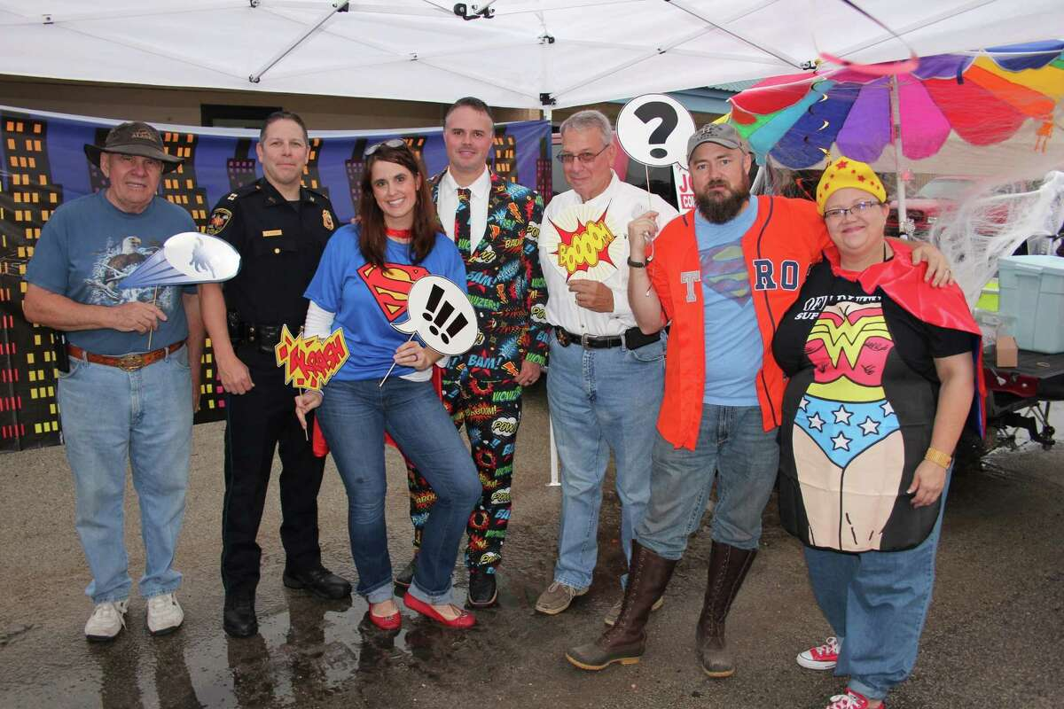 The Justice League - Attorneys Jennifer Bergman and Donny Haltom, and Liberty County Sheriff Bobby Rader - won first place in the 2015 Treat Street booth contest. Bergman and husband, Zach Harkness, brought their antique fire truck as a backdrop for all their superhero costumes and decorations. Pictured with the Justice League team are Jim Carson of the Greater Cleveland Chamber of Commerce and Capt. Scott Felts of Cleveland Police Department (first and second from left), who acted as judges for the booth contest Saturday night.