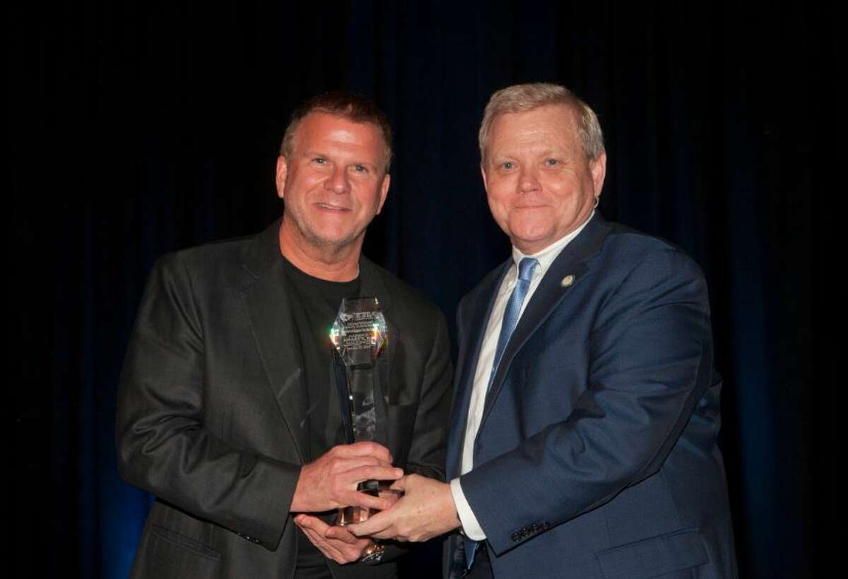 Landry's, Inc. chairman and CEO Tilman Fertitta, left, receives the Texas Travel Industry Association's Heritage Award from association president and CEO David Teel during the group's annual summit in Houston on Oct. 11, 2016.