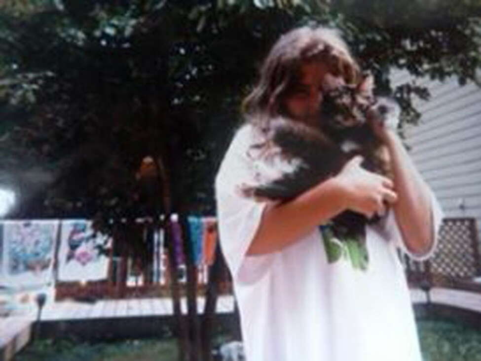 Lindsay Ruiz as a young girl with Cinnoman, a Maine Coon cat she got for her 9th birthday. The cat died last month at 18 and Ruiz memorialized the cat with a paid death notice in the Times Union, online pet bereavement sites and a Facebook page (Paul Grondahl / Times Unoin)