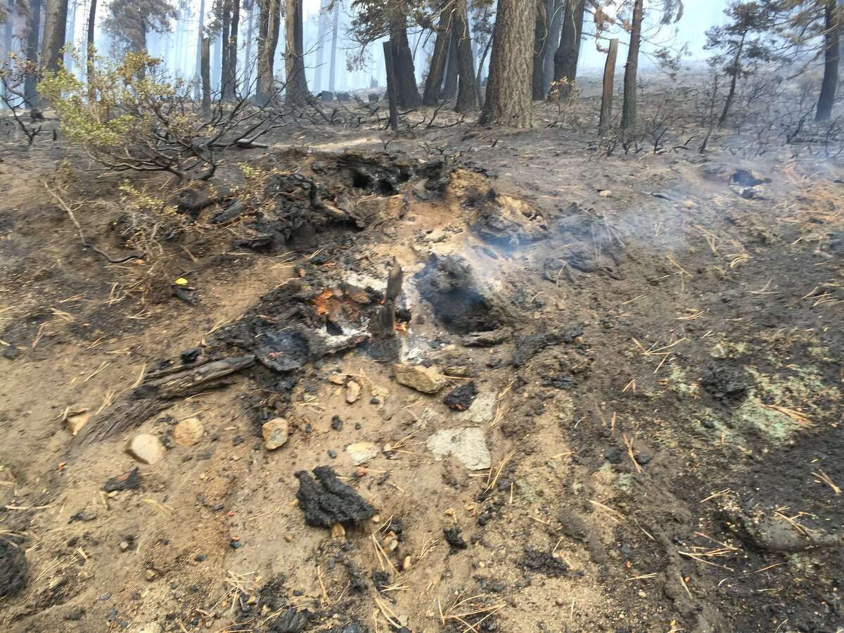 Smoldering vegetation marks the path of the South Lake Tahoe-area fire as crews continued to battle it on Friday.