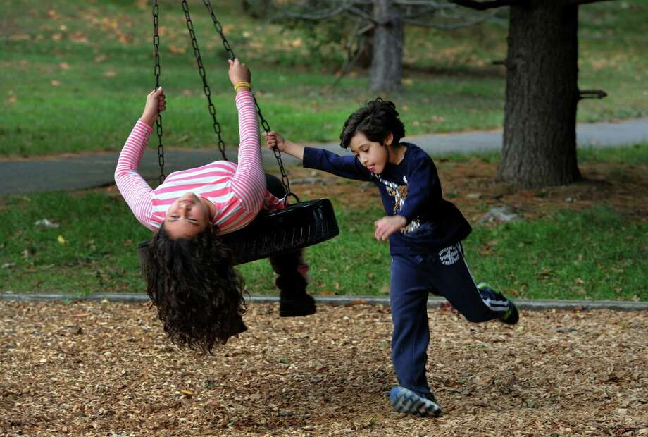 Gabriel Pereira, 6, pushes his sister Victoria, 11, on the tire swing at Tunxis Hill Park in Fairfield, Conn. on Wednesday October 12, 2016. Photo: Christian Abraham / Hearst Connecticut Media / Connecticut Post