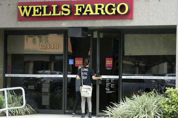 FILE - In this Thursday, Sept. 22, 2016, file photo, customers walk into a Wells Fargo bank in Pembroke Pines, Fla. On Friday, Oct. 14, 2016, Wells Fargo reports financial results. (AP Photo/Lynne Sladky, File)