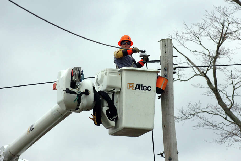 A member of a power crew contracted by the United Illuminating Co. works to repair power lines after damage from Hurricane Sandy in Milford in 2012. Photo: Christian Abraham / File Photo / Connecticut Post