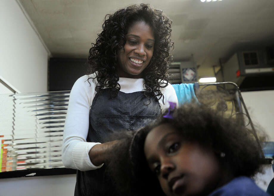 Cheryl McLaughlin-Williams braids the hair of client Keshima Richards, 10, at her Cherr's Beauty Salon at 386 Granfield Avenue in Bridgeport, Conn. on Wednesday, October 12, 2016. McLaughlin-Williams is celebrating 20 years in business this year. Photo: Brian A. Pounds / Hearst Connecticut Media / Connecticut Post