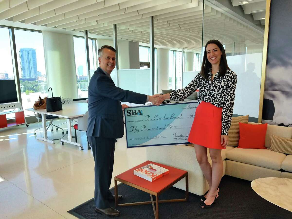 Carolyn Rodz, right, founder of Circular Board, receives a check for $50,000 from Tim Jeffcoat, Houston district director for the U.S. Small Business Administration. Circular Board won the national SBA's annual growth accelerator competition.