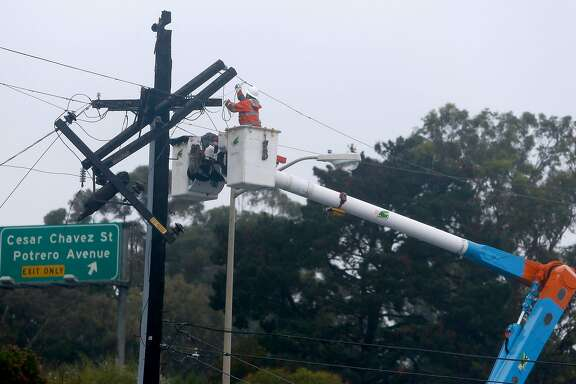 A PG&E crew repairs a broken power pole on the 200 block of Bayshore Boulevard during the first rainstorm of the season in San Francisco, Calif. on Friday, Oct. 14, 2016.