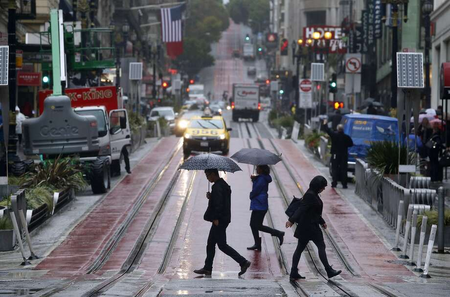 People cross Powell Street at Ellis Street during the first rainstorm of the season in San Francisco on Friday, Oct. 14, 2016. Photo: Paul Chinn, The Chronicle