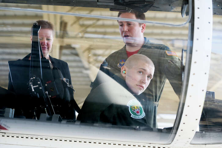 """Jake Larner, 16, looks out of the copit of a T-6 Texan with Air Force Capt. Vernon Work and his mother, Kristie Davidson, as a """"Pilot for a Day"""" with the 560th Flying Training Squadron at Joint Base San Antonio - Randolph on Friday, Oct. 14, 2016.  Larner, living with lymphoma, spent the day learing about life as an Air Force pilot including suiting up as a pilot, touring  a static T-38C Talon and other planes, riding a flight simulator and being honored at a reception at the 560 FTS.  Since the start of the program in 1994, over 100 children have been """"Pilot for the Day.""""  MARVIN PFEIFFER/ mpfeiffer@express-news.net"""