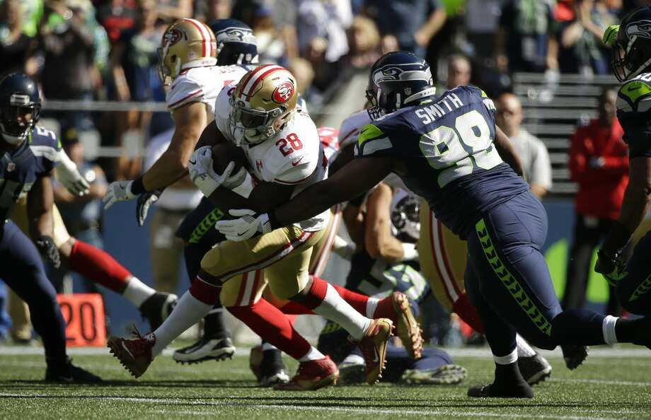 Seattle Seahawks defensive tackle Garrison Smith (98) tackles San Francisco 49ers running back Carlos Hyde (28) during an NFL football game, Sunday, Sept. 25, 2016, in Seattle. (AP Photo/Ted S. Warren) Photo: Ted S. Warren/AP