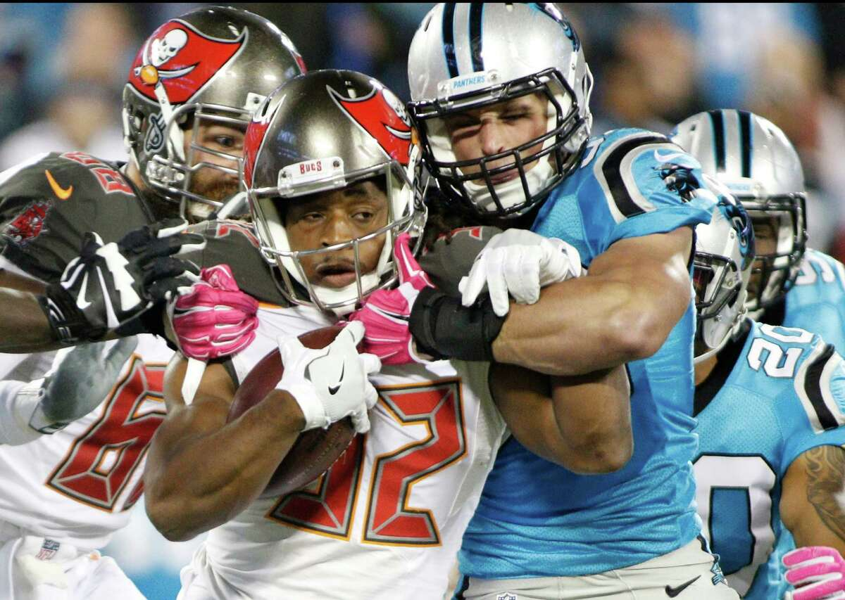FILE - In this Oct. 10, 2016, file photo, Tampa Bay Buccaneers' Jacquizz Rodgers (32) is stopped by Carolina Panthers' Luke Kuechly (59) during an NFL football game in Charlotte, N.C.