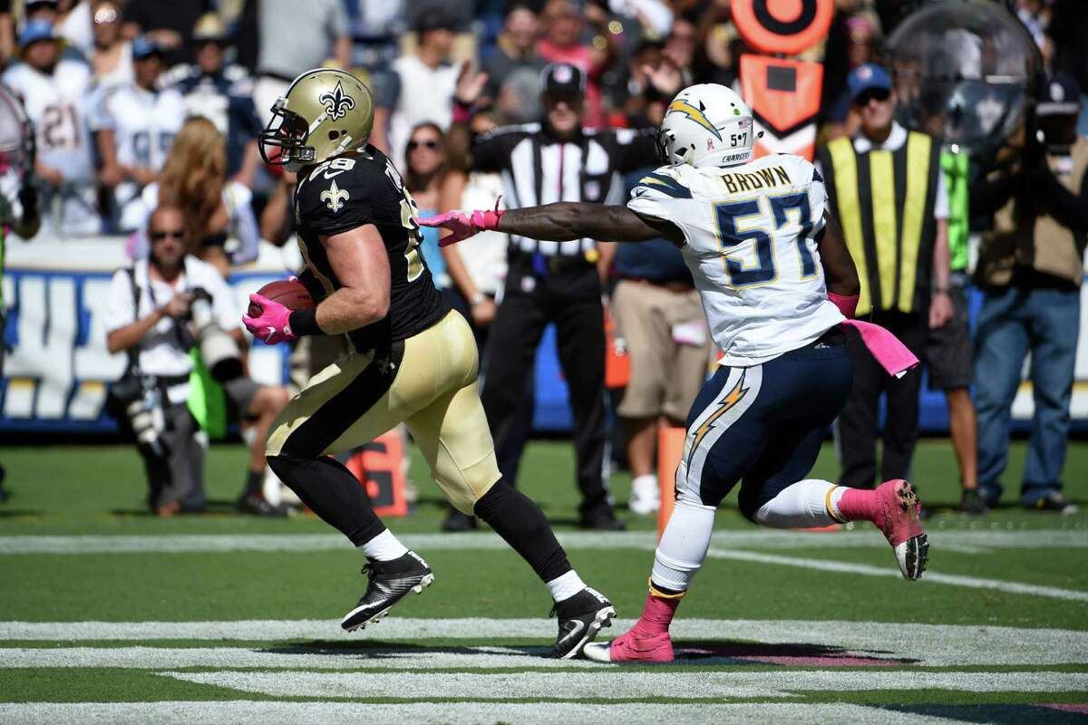 FILE - In this Oct. 2, 2016, file photo, New Orleans Saints fullback John Kuhn scores a touchdown in front of San Diego Chargers outside linebacker Jatavis Brown (57) during an NFL football game in San Diego. On its face, the match-up of the Saints (1-3) and Panthers (1-4) has the look of a game between two struggling teams who very well might be going nowhere this season. On the other hand, it could make for a desperate, high-stakes affair, given both teams are trying to salvage their season and believe it is still early enough to do so.