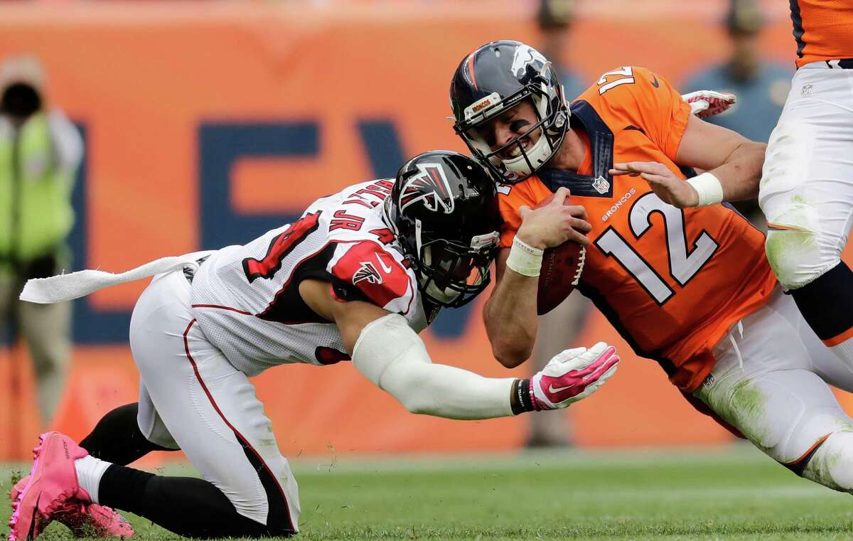 FILE - In this Oct. 9, 2016, file photo, Denver Broncos quarterback Paxton Lynch (12) is hit by Atlanta Falcons outside linebacker Vic Beasley (44) during an NFL football game in Denver. The Falcons face the Seattle Seahawks this week. (AP Photo/Jack Dempsey, File)