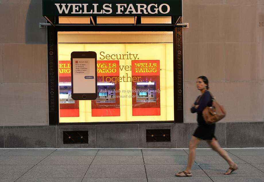 (FILES) This file photo taken on October 5, 2016 shows a woman walking past a Wells Fargo bank in Washington, DC. Large US banks reported lower third-quarter earnings on October 14, 2016 but beat analyst expectations, as Wells Fargo pledged anew to win back consumer trust after a bogus accounts scandal. Profits from JPMorgan Chase, Citigroup and Wells Fargo for the third quarter were lower compared with the year-ago period, revealing anew the drag on margins from ultra-low interest rates.  / AFP PHOTO / ANDREW CABALLERO-REYNOLDSANDREW CABALLERO-REYNOLDS/AFP/Getty Images Photo: ANDREW CABALLERO-REYNOLDS, AFP/Getty Images