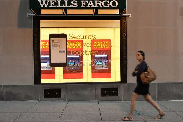 1of2FILES This File Photo Taken On October 5 2016 Shows A Woman Walking Past Wells Fargo Bank In Washington DC Large US Banks Reported Lower