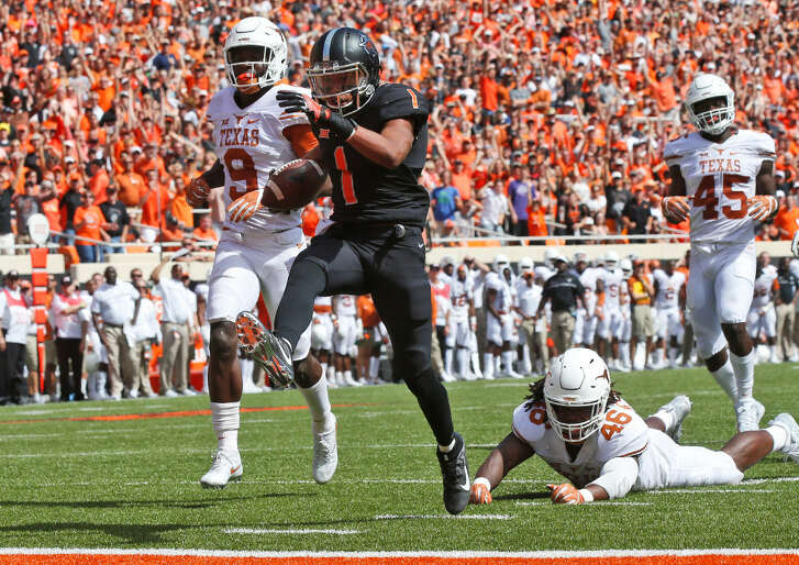 Oklahoma State wide receiver Jalen McCleskey (1) heads into the end zone with a touchdown in front of Texas cornerback Davante Davis (9), Malik Jefferson (46) and Anthony Wheeler (45) in the second quarter of a game in Stillwater, Okla., Saturday, Oct. 1, 2016.